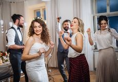 A young bride with other guests dancing on a wedding reception. A young cheerful bride with other guests dancing on a wedding reception royalty free stock image