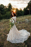 Young bride outside on a summer meadow at the sunset Royalty Free Stock Photography