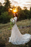 Young bride outside on a summer meadow at the sunset Stock Photos
