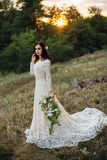 Young bride outside on a summer meadow at the sunset Royalty Free Stock Image