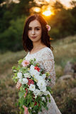 Young bride outside on a summer meadow at the sunset Royalty Free Stock Images
