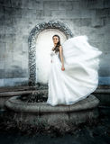 Young bride posing at old castle while wind blows her veil Royalty Free Stock Photo