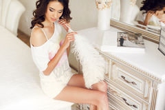 The young bride preparing for the wedding night. Young bride - brunette with long curly hair, bridal wreath on his head in the night white shirt with a large stock images