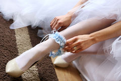 Young bride putting on blue garter Stock Images
