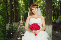 Young bride with red bouquet Stock Image