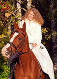 Young bride riding on sorrel horse Stock Photography