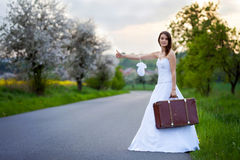 Young bride on the road with a suitcase Stock Photos