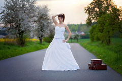 Young bride on the road with a suitcase Royalty Free Stock Photography