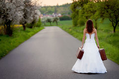 Young bride on the road with a suitcase Royalty Free Stock Photo