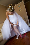 Young bride setting the garter. Portrait of young bride setting the garter straight on her leg while preparing for wedding Royalty Free Stock Photography