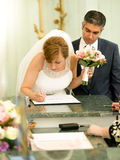 Young bride signing wedding contract at registry office Stock Photography