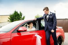 Young bride sits behind the wheel of a red sports car. The bride sits behind the wheel of a red sports car and looks at the groom stock photography