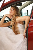 Young bride sits in car Stock Photography