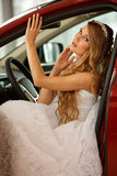 Young bride sits in car Stock Image