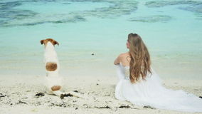 Young bride sitting on the beach with homless dog. Beautiful woman in white dress with a dog on tropical beach enjoying a beautiful view of the ocean stock footage