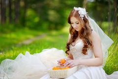 Young bride sitting on a grass Royalty Free Stock Photos