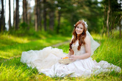 Young bride sitting on a grass Royalty Free Stock Images