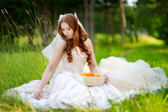 Young bride sitting on a grass Stock Photos