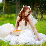 Young bride sitting on a grass Stock Photo