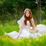 Young bride sitting on a grass Royalty Free Stock Image