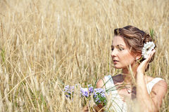Young bride sitting in the grass. Young bride wearing a white wedding dress sitting in the grass Royalty Free Stock Photo
