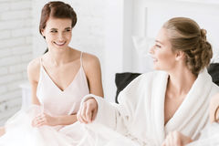 Young bride sitting with her bridesmaid at home Stock Images