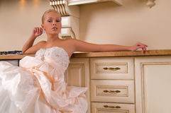 Young bride sitting on the kitchen Stock Photography