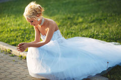 Young bride sitting on the lawn. Young bride in a beautiful white dress sitting on the lawn in the summer on a sunny day Stock Photography