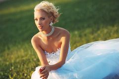 Young bride sitting on the lawn. Young bride in a beautiful white dress sitting on the lawn in the summer on a sunny day Royalty Free Stock Photos