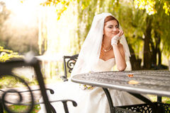 Young bride sitting on summer terrace at park Stock Photos