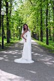 Young bride standing in an alley in the park Royalty Free Stock Image