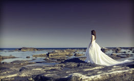 Young bride standing on a cliff at the sea Royalty Free Stock Photography