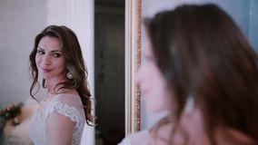 Young bride standing in front of mirror, then turn and looking at camera. Woman looks at reflection before wedding. stock video
