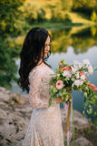Young bride standing on rocky river bank, sunset Royalty Free Stock Photos
