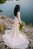 Young bride standing on rocky river bank, sunset Stock Photos