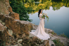 Young bride standing on rocky river bank, sunset. Young bride in wedding dress standing on rocky river bank, sunset Stock Images