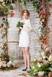 Young bride is standing under the arch of autumn plants Stock Images