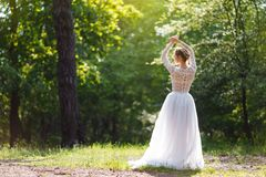 A young bride stands in the park with her back. Pretty unusually posing on camera.  Stock Photos