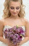 Young bride in studio admiring exquisite bouquet Stock Photos