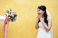 A young bride in surprise. With an offered beautiful bouquet Stock Photography