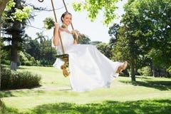 Young bride swinging in garden Stock Image