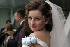 Young bride in a veil. The bride has looked back on visitors during walk after wedding ceremony Stock Image