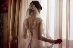 Young bride waiting for her groom. And watching in the window Stock Image