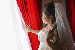 Young bride waiting near window. Young enchanted bride waiting for her groom near window with red curtains Royalty Free Stock Image
