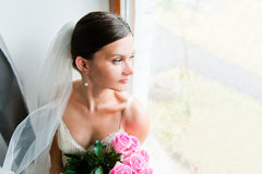 Young bride waits for groom near the window Stock Photo