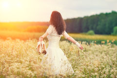 Young bride walking on the flower meadow Royalty Free Stock Image