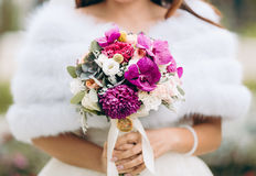 Young bride on wedding day holding bouquet. Against blurry background stock photo