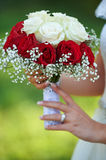 Young bride on wedding day holding bouquet. Against blurry background stock photos