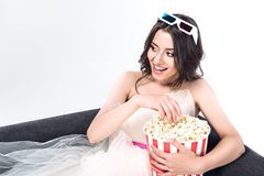 Young bride in wedding dress and 3d goggles holding bucket of popcorn and sitting on couch. Isolated on white stock photo