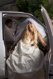 Young bride in wedding dress getting off car. Young Caucasian happy women in white gorgeous wedding gown sitting in car Stock Image